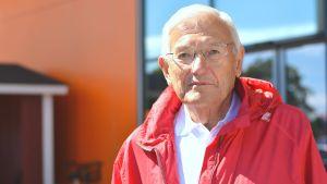 Närbild, porträtt, av Rune Westerholm, äldre man med glasögon och röd jacka.