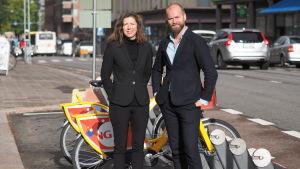 Marianne Weinreich och Lars Strömgren vid en station för gula lånecyklar.