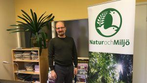 En man står bredvid en krukväxt på ett kontor.