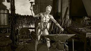 Robotiksi vartalomeikattu malli esittää takovaa seppää pajassa