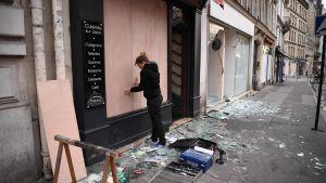 En kvinna i Paris ersätter ett krossat skyltfönster med plywoodskivor på söndag morgon.