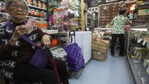 En gråhårig kinesisk kvinna väntar i en apotek för traditionell kinesisk medicin