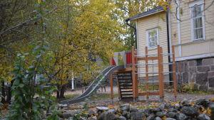 En klätterställning med rutschkana på gården framför ett gult hus.