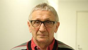 En äldre herreman med glasögon och vitt hår står i en korridor.