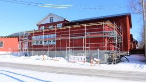 En röd träbyggnad med byggställningar runt.