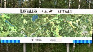 En karta som med en bild tagen från luften visar hur den nya friluftsleden i Raseborg, Banvallen, löper från Karis via Billnäs och Åminnefors till Skuru och Fiskars bruk.