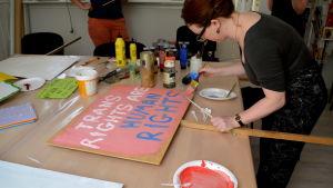 En kvinna målar en pride skylt