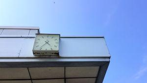 En analog väggklocka på fasaden av en sliten vit marmorbyggnad. Det är antagligen en 1970-talsklocka som finns kvar på busstationens vägg i Karis.