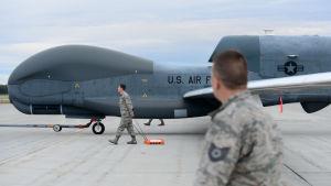 Obemannad drönare RQ-4 Global Hawk med servicepersonal på flygplats i Alaska.