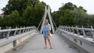 En kvinna står på en gångbro.