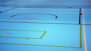 Golv i en idrottssal. Golvet är blått med olika färgers linjer.