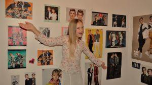 Ida Mansikka står mitt i bilden och ser in i kameran. Hon ser glad ut och har armarna utsträckta. Bakom henne har hon en vägg med plancher på den norska popduon Marcus & Martinus.