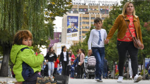 Människor går framför en valaffisch i Pristina.