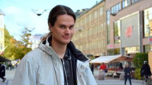 en man i grå jacka står vid gågatan i Åbo där människor går och cyklar omkring