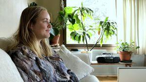 kvinna sitter i en soffa i sitt vardagsrum med växter runtom