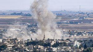 Rök stiger från staden Ras al-Ain. Staden är fotad med en drönare eller från en helikopter.