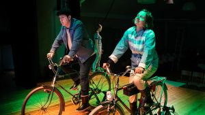 Presidentparet eller deras alteregon tar sig en cykeltur i lokala landskap. (Matti Raita och Sanna Hietala).