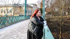 Nainen nojaa sillan kaiteeseen