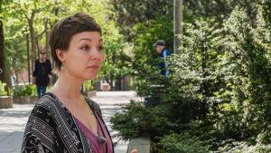 Nuori nainen lähikuvassa, taustalla katu, ihmisiä ja pensaita.