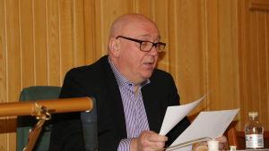En skallig man med glasögon sitter vid ett bord och bläddrar i papper.