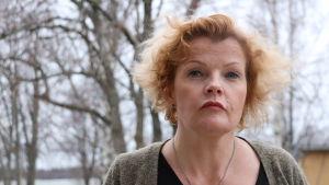 En kvinna i 50-årsåldern med axellångt rödbrunthår. I bakgrunden syns träd.