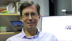 En man i ljusblå skjorta och glasögon tittar in i kameran.