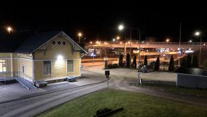En gul träbyggnad intill järnvägsspår och en bro.