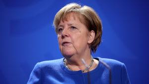 Angela Merkel, blå tröja framför en blå bakgrund. Framför mikrofoner.