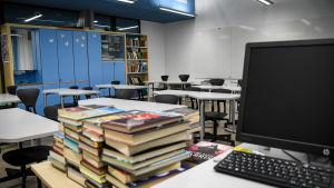 Böcker och laptop i förgrunden, tomt klassrum i bakgrunden