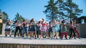 Skådespelare står i klädda 80-talskläder och dansar på en utomhusscen.