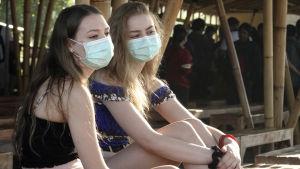Två unga flickor sitter på en strand med munskydd för munnen.
