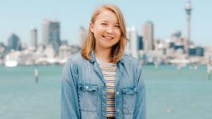 Au pairit Uudessa-Seelannissa -sarjan Sini seisoo meren rannalla hymyillen kameraan.
