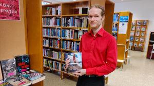 En man står och håller fram en bok i ett bibliotek.