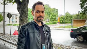 Björn Näse står på trottoaren med trafik i bakgrunden