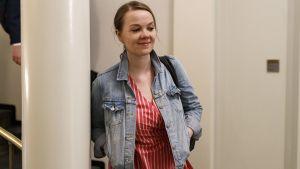 Katri Kulmuni på väg ut från riksdagen, i blå jeansjacka.