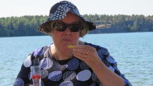 En lite äldre kvinna i solhatt och sommarklänning som dicker bubbel och äter salta snittar. Hav och sol i bakgrunden. Sommar.