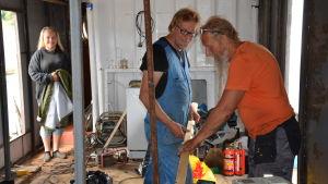 Insidan av en båt som håller på att renoveras. I förgrunden två män och i bakgrunden en kvinna.