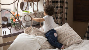 Barn står i sängen och tittar ut genom fönstret.