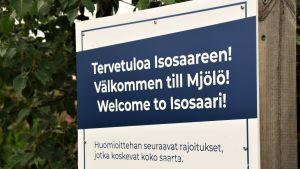 """En vit skylt med texten """"Välkommen till Mjölö"""" på blå bakgrund, skrivet på finska, svenska och engelska. Bakom sklyten syns gröna löv."""