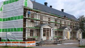 En byggnad som renoveras. Byggställningar är placerade runt huset.