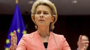Ursula von der Leyen i närbild. Bakom henne syns en EU-flagga och en svart bakgrund. Von der Leyen talar i mikrofon och har händerna uppe, hon har en laxröd kavaj på sig.