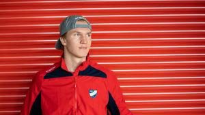 Anton Lundell står framför en röd vägg.