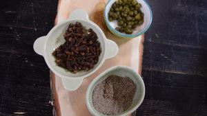 Kaprista, mausteneilikkaa ja kardemummaa kulhoissa pöydällä