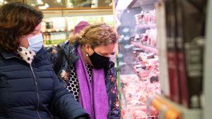 Två kvinnor väljer nåt från köttdisken.