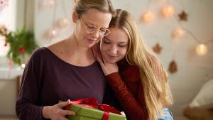 mamma och dotter håller i ett julpaket
