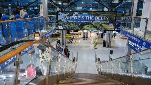 Personer i en rulltrappa på Helsingfors-Vanda flygplats.