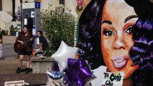 Stor väggmålning av Breonna Taylor. I förgrunden syns ballonger.