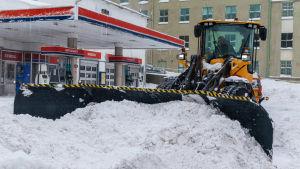 Traktor röjer snö på gård.