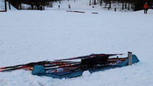 En väska med skidor ligger i snön.