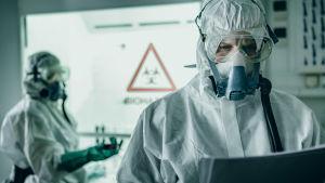 Suojapukuiset henkilöt katsovat vakavina papereitaan kliinisessä ympäristössä.